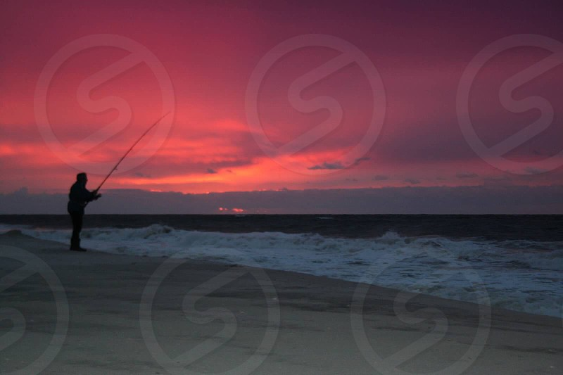 man silhouette holding fishing rail photo