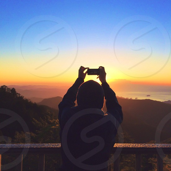 man taking picture of sunset photo