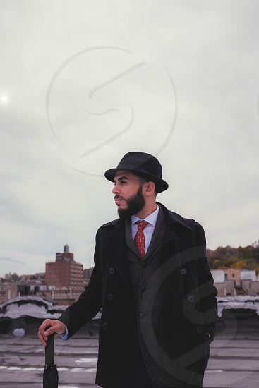 Manny over looking New york on the roof top waiting for rain. dapper best dressed style fashion mens fashion men wear beard hat tie suspenders photo