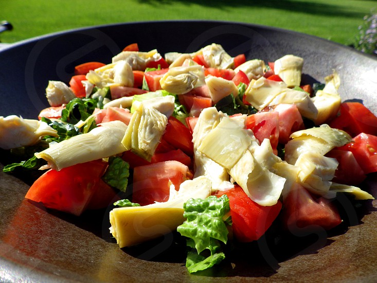 Artichoke and tomato salad in a bowl on a picnic table in the summer sun photo