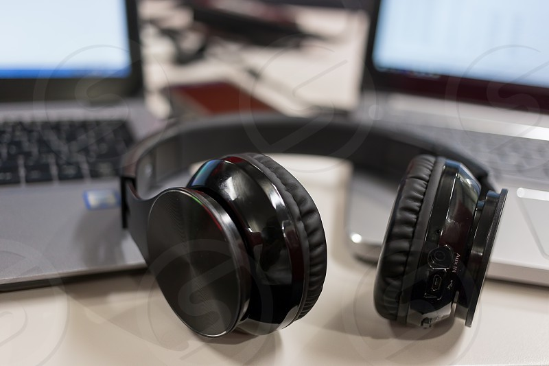 Laptops and bluetooth headphones in an office environment photo