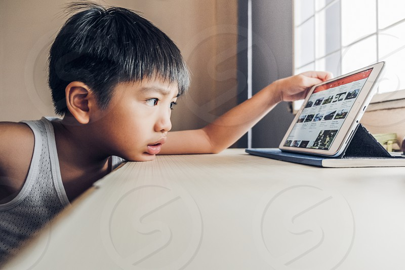Side view of young boy using mobile device next to windows in room photo