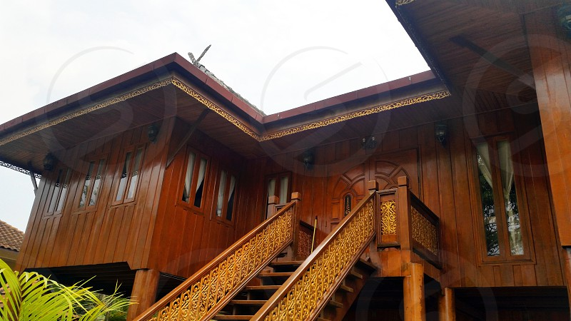 brown wooden house with front stair under white sky during daytime photo