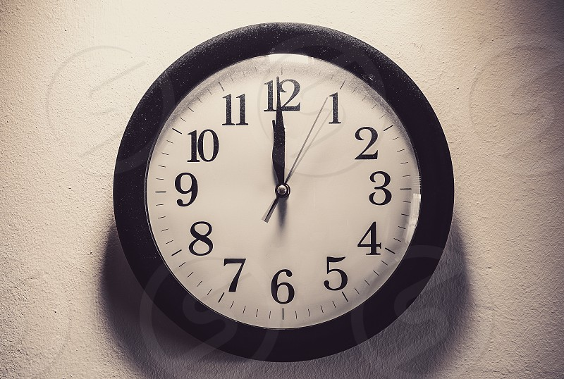 Details of a dusty clock on the white wall retro style.  photo