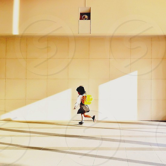girl in school uniform with yellow backpack running photo