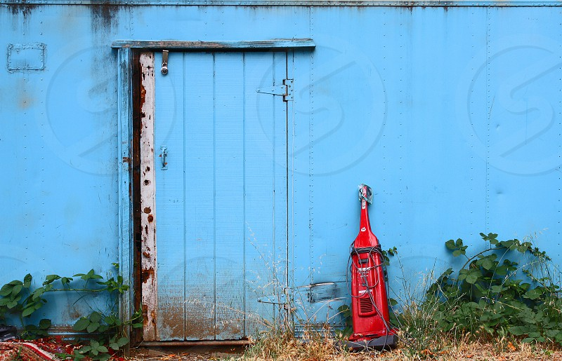Old wooden door on a weathered blue building; a broken red vacuum leans against the side. photo
