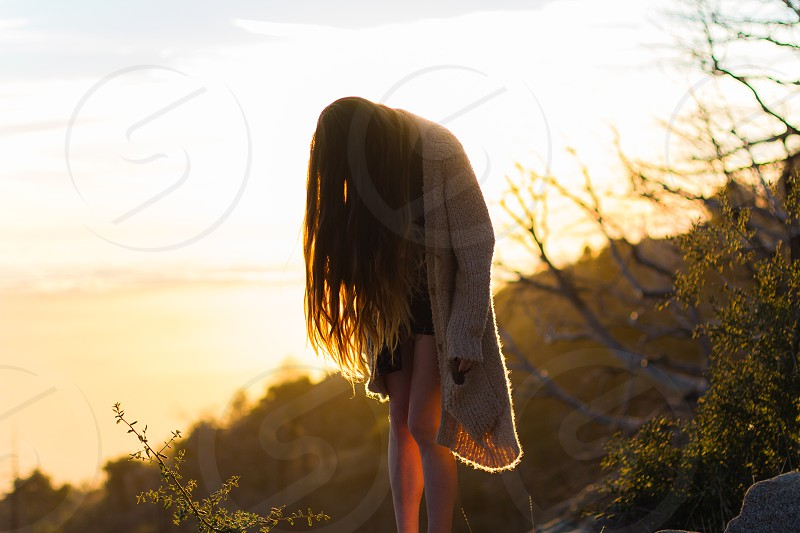 woman with long blonde hair in long cocoon cream cardigan and black shorts on hill at sunset photo
