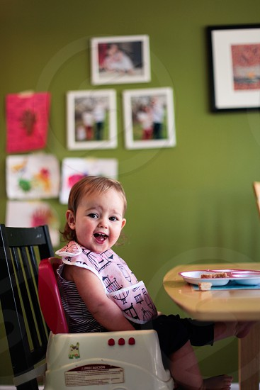 smiling toddler girl sitting in a high chair at a table with photos and art hanging on a green painted wall in the background photo