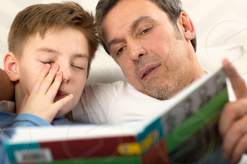 Close-up shot of a father reading a book to the son who is already sleepy and rubbing his eyes photo