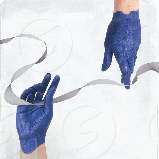 person with blue hands touching gray ribbon photo
