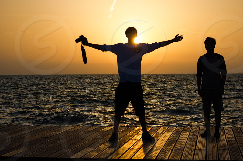 man in gray shirt holding dslr camera standing beside person on wooden pier during yellow sunset photo