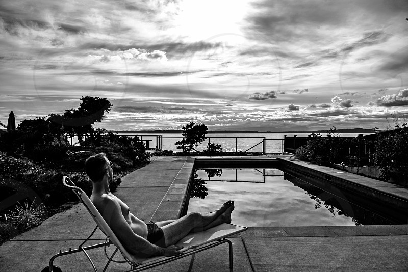 Black and white with added Grain. Poolside evening man lounging inspiring  photo