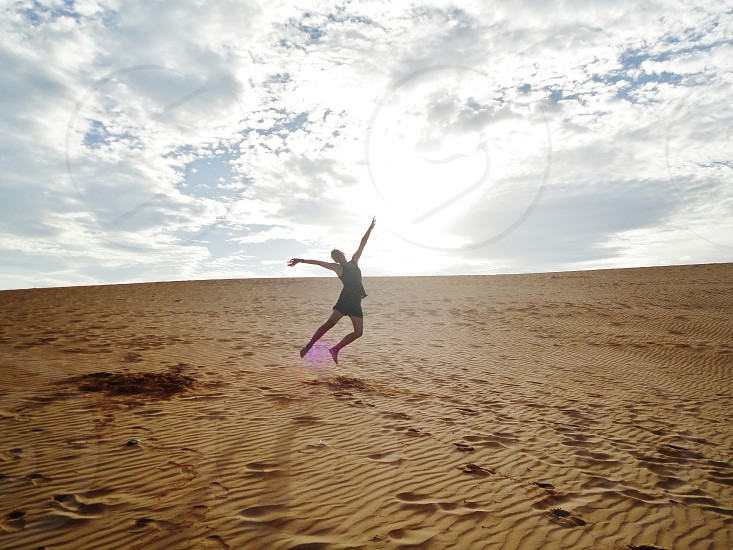 person jumping on brown desert sand during daylight photo