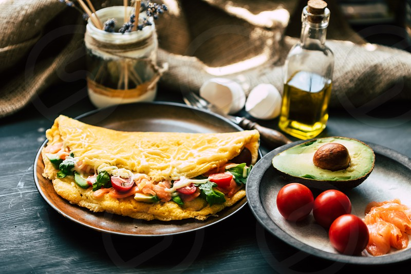 fresh fluffy omelette with salmon tomatoes avocado cheese and rucola on a wooden rustic table photo