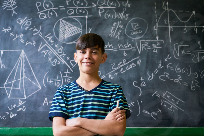 Concept on blackboard at school. Young people student and pupil in classroom. Smart hispanic boy writing math formula on board during lesson. Portrait of male child smiling looking at camera photo