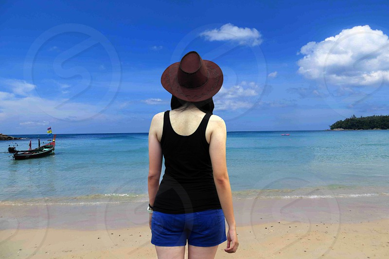 dark haired woman in black tank top and blue shorts wearing brown wide brim hat standing on sandy beach facing blue ocean with fishing boat under blue and white cloudy sky photo