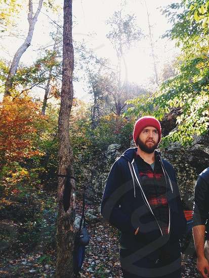 man wearing red beanie walking on forest photo