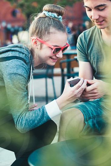 Couple of friends teenage girl and boy  having fun with smartphones sitting in center of town spending time together photo