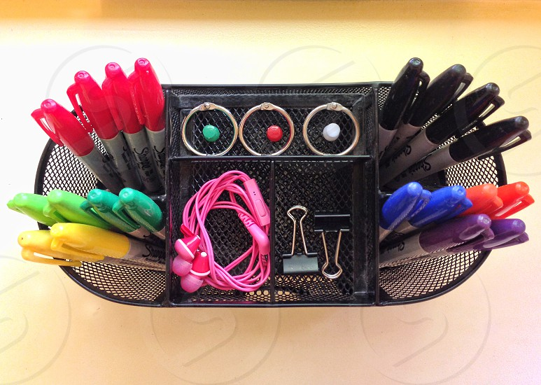 Seen from above colored pens ear buds and clips are neatly arranged in a  container photo