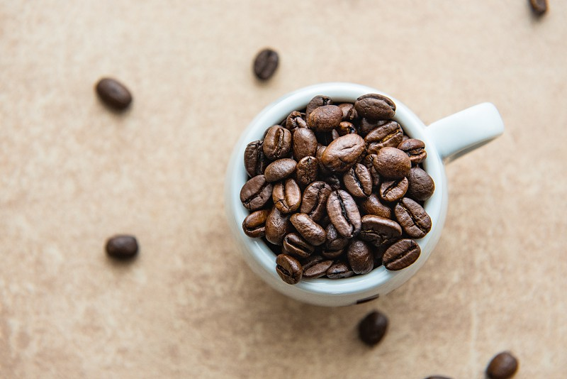 Cup of coffee full of coffee beans. photo