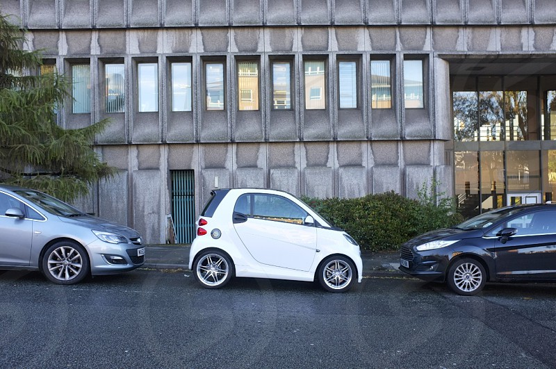 White Smart Brabus car in small parking gap. photo