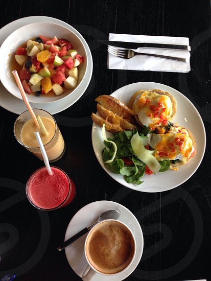 Egg Benedict fruits salad juices coffee for breakfast photo