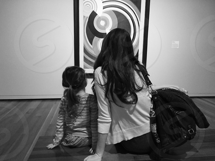 woman wearing cardigan sitting beside girl in stripe sweater facing abstract painting in grayscale photo