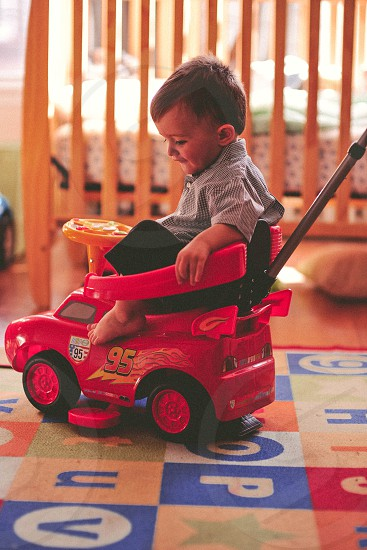 boy in gray shirt sitting on the push car inside the room in a distance of a crib photo