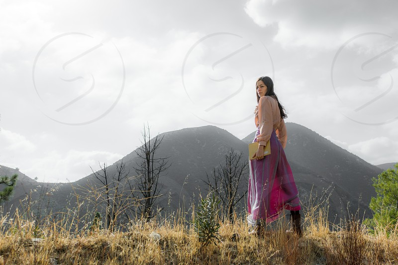 Girl in fantasy outfit looking back while standing atop a mountain ridge photo