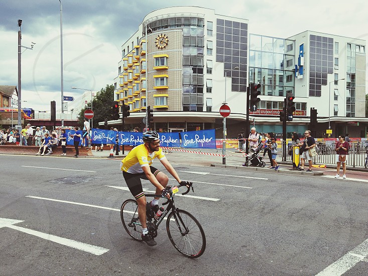 cyclist traveling on road near concrete building with people watching during daytime photo