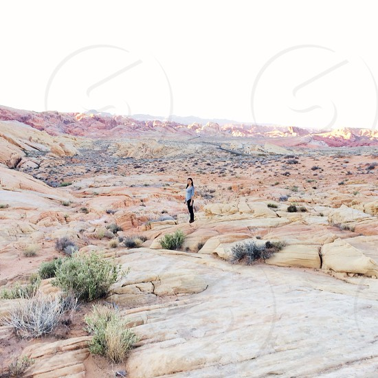 woman standing on red and brown rocks in the desert photo