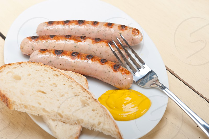 traditional fresh German wurstel sausages grilled with yellow mustard  photo