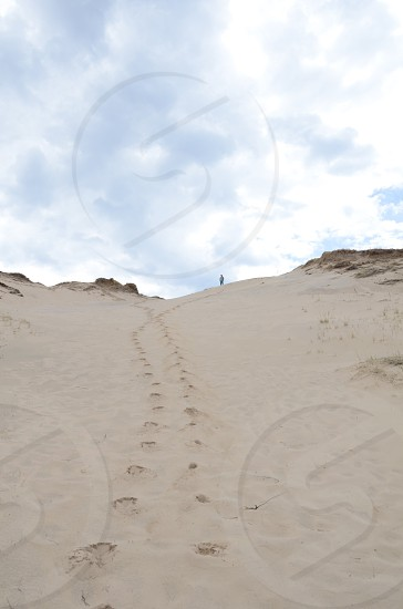 Tiny man standing on top of sand dune footprints photo
