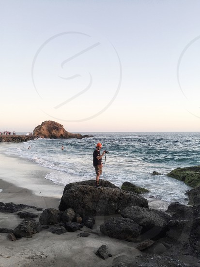 man in black t-shirt wearing orange cap holding black dslr camera standing on black boulder on beach shore near blue ocean water under blue sunny sky photo