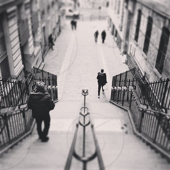 grayscale people walking along the street and stairs photography photo