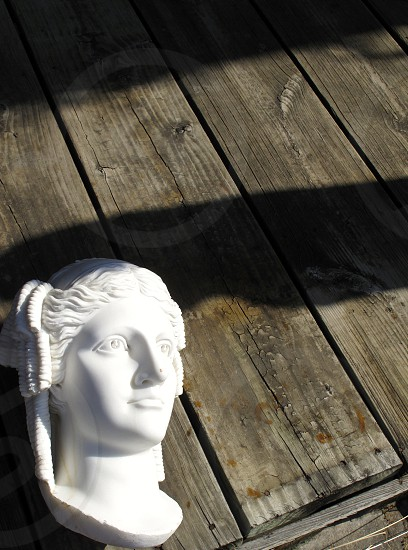white marble statue wooden floors floorboards woman head shadows photo