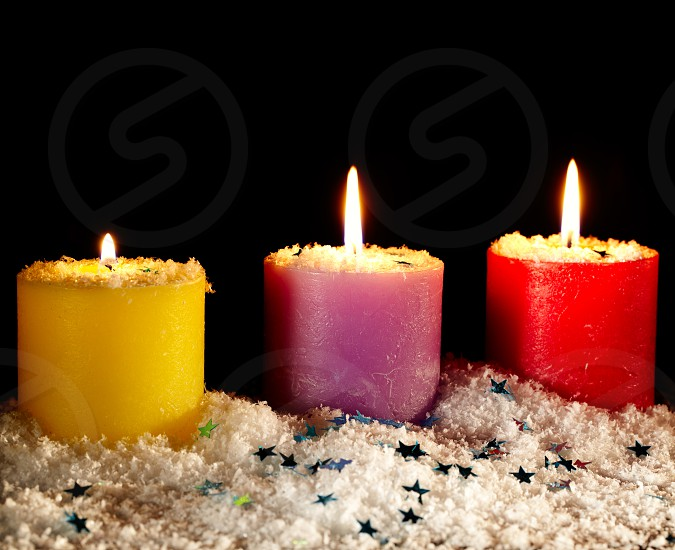 Three festive candles covered with artificial snow on a black background. Frontal view with copyspace. photo