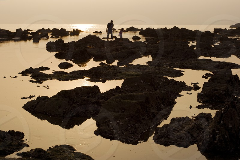Tidepools at Shonan Beach near Kamakura Japan.  Crawling around volcanic rocks examining ocean life within the tidepools is a favorite activity among Japanese families -  teaching the kids about nature.  In such an idyllic scene it is hard to believe that Tokyo is only minutes away. photo