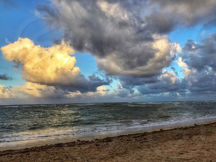 The ocean sunset. The setting sun highlights some cumulus clouds with golden rays the other clouds are dark and look like thunderstorms. photo