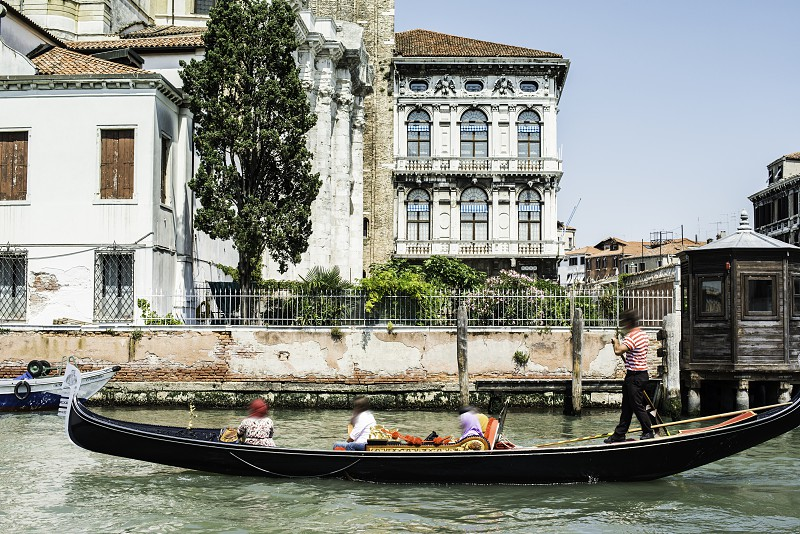 Ancient buildings and boats in the channel in Venice. Gondolier photo