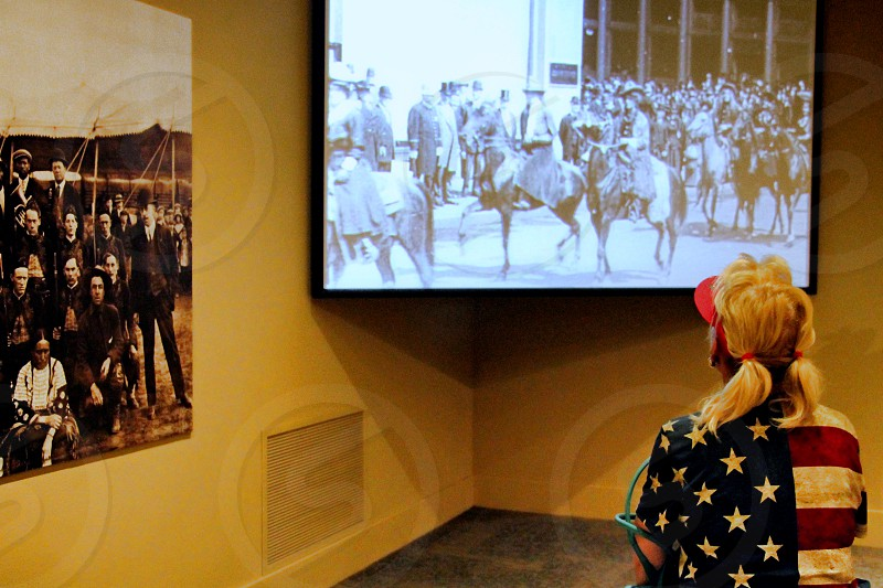 Seen from behind inside a museum a woman in a flag patterned shirt watches a movie photo