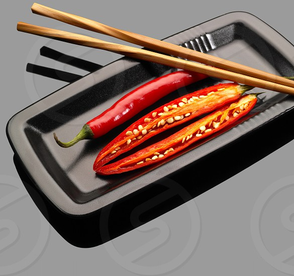 fresh red chili peppers on a plate with chopstikcs over grey reflective surface photo
