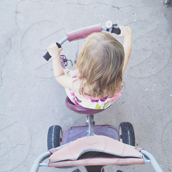 little girl riding on a tricycle photo