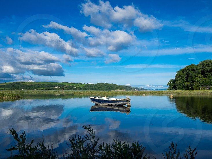 The Blue Boat and Reflections - Laugharne Estuary. photo