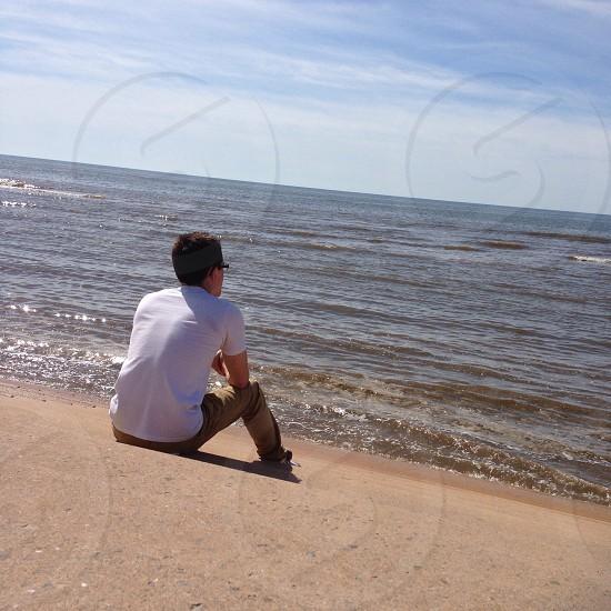 man wearing white shirt sitting in sea shore photo