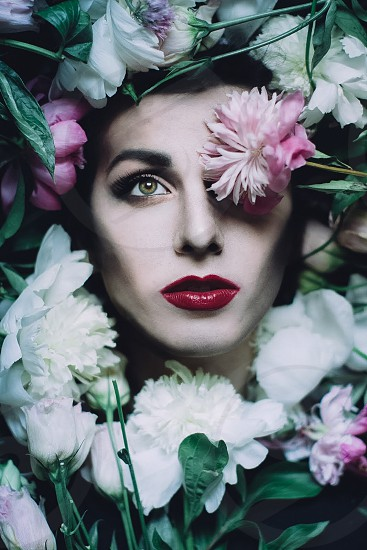 pink and white flower covering left eye of a woman photo