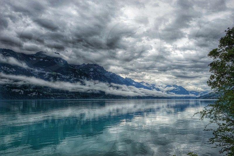 Lake Thun in Switzerland a storm rolling in over the mountains reflected in the lake photo