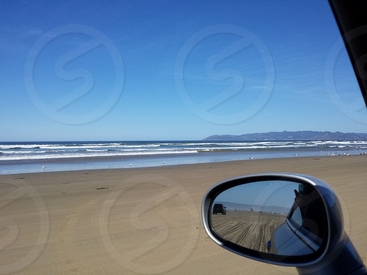 Driving on the beach by the ocean photo
