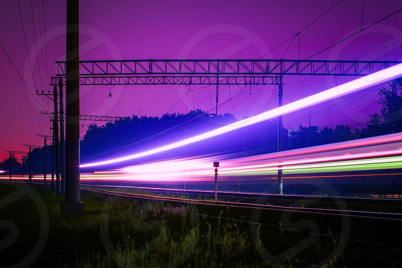 photograph of train passing on railway during nighttime photo