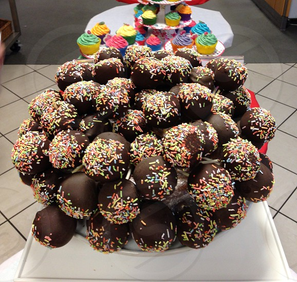 display of chocolate covered cakepops and mutli colored cupcakes photo